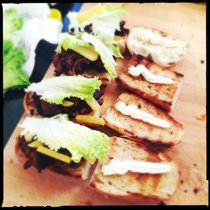 Pork Belly sandwich, with lettuce, pickled radish, and mayo on a baguette